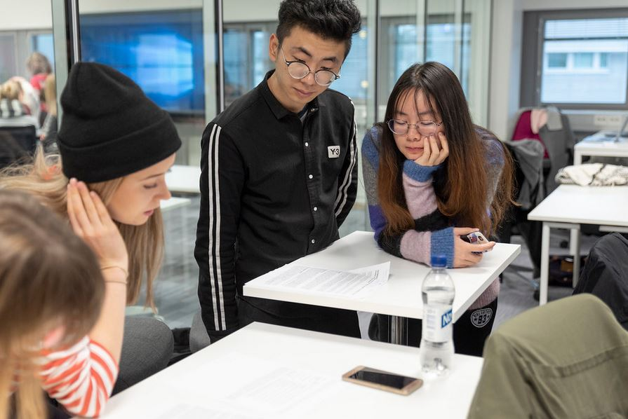 Opiskelijat tutkivat yhdessä pöydällä olevaa paperia .