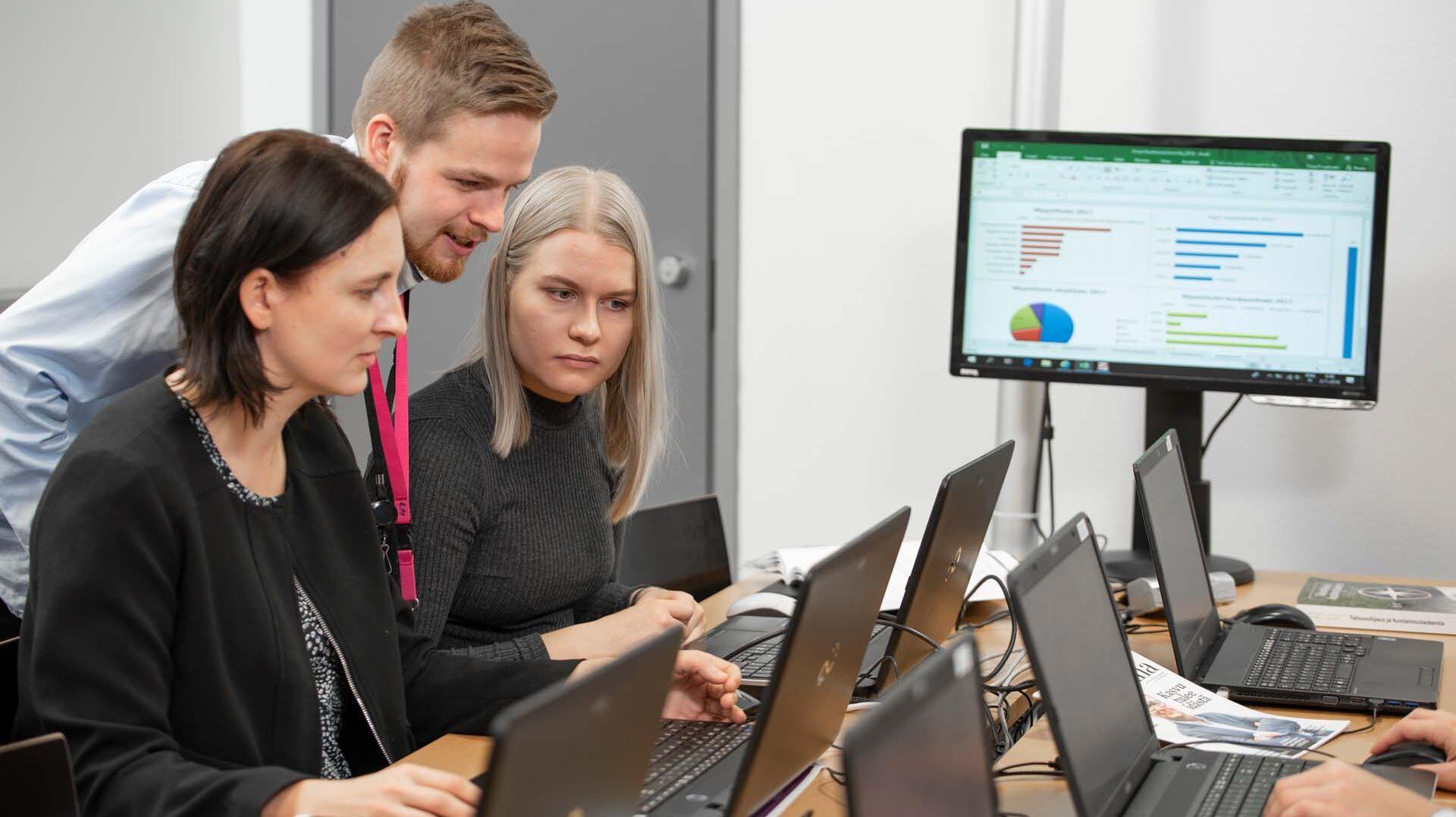 Kolme opiskelijaa työsnkentelee tietokoneilla.