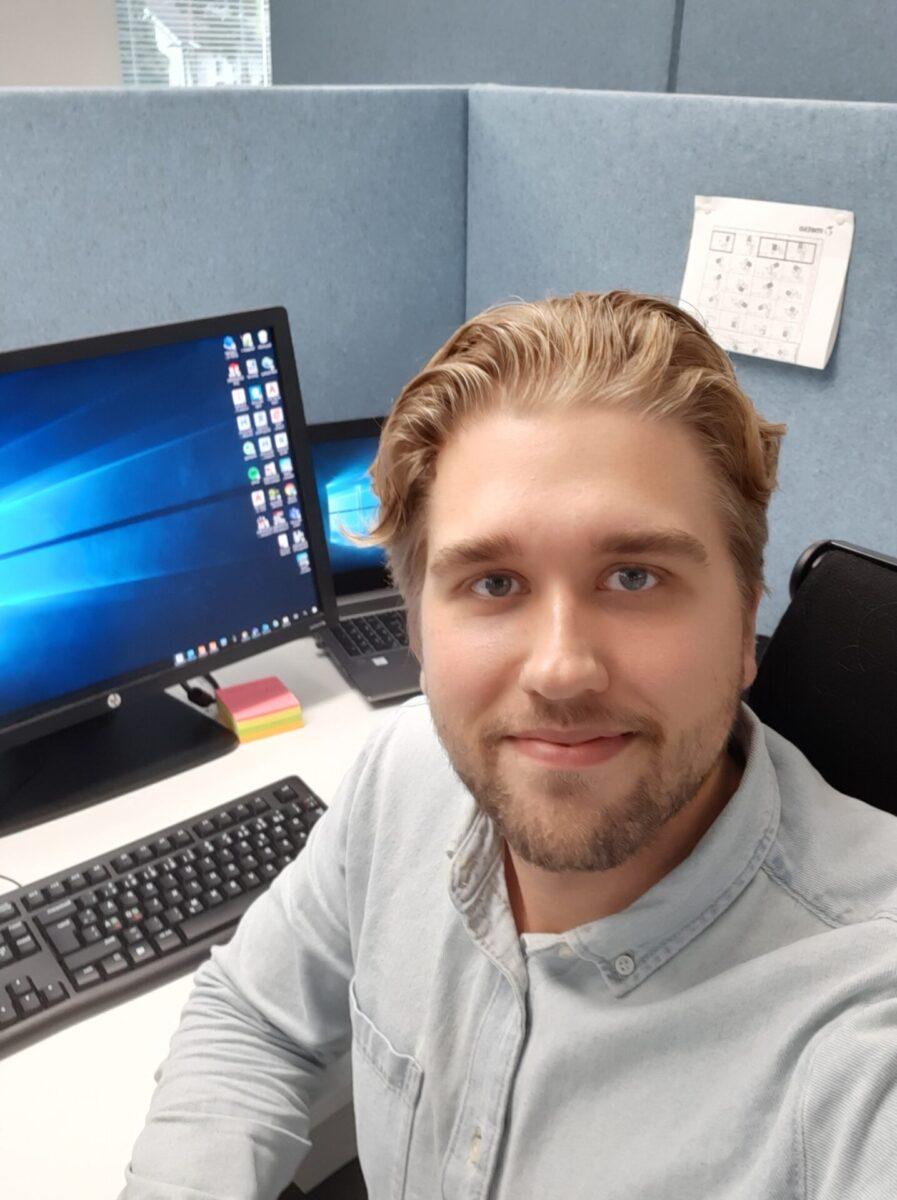 Mies työpisteellä tietokoneen ääressä.