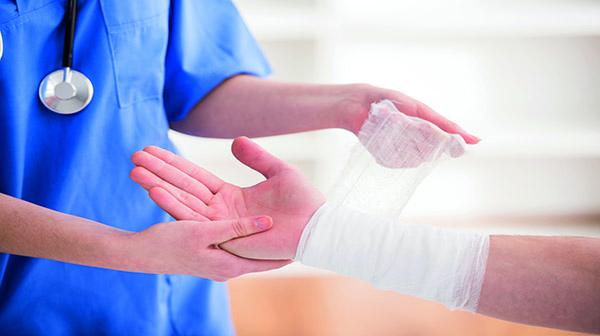 hoitaja käärii sidettä käden ympärille