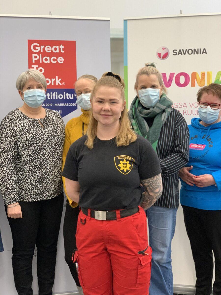 Helpottunutta opiskelijapalveluiden väkeä, edessä Karoliina Ollanketo. Kuvassa seisoo viisi ihmistä, Karoliina seisoo etualalla ja hymyilee kameralle.