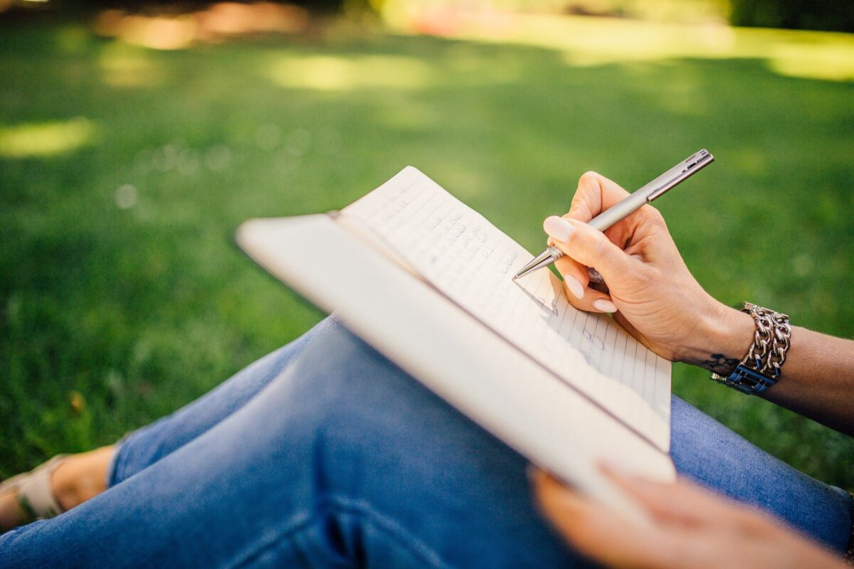Nainen kirjoittaa tekstiä muistivihkoon.