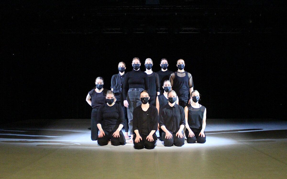 Tanssijat istuvat tai seisovat yhdessä rykelmässä maskit kasvoillaan, valo tekee kuvasta dramaattisen ja sen sävyt ovat hyvin mustavalkoiset.