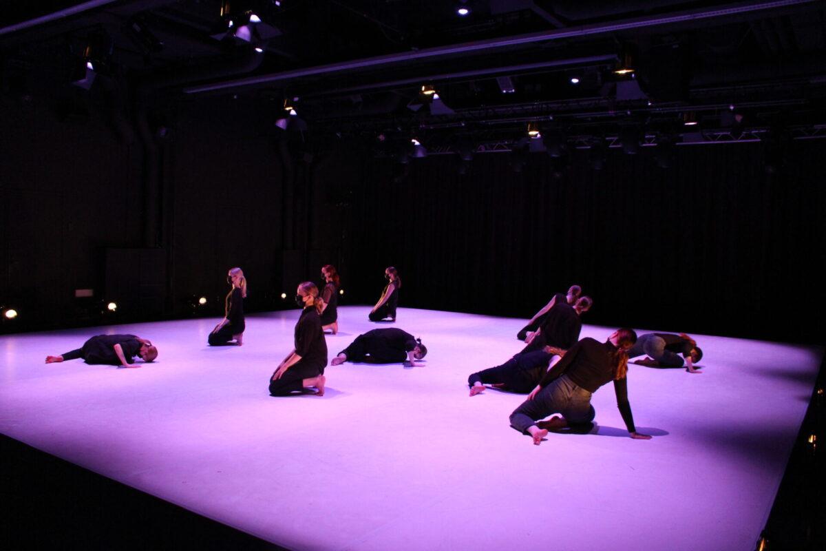 Tanssijat ovat puoliksi makaavissa asennoissa tai istumassa pitkin lavaa, valot tekevät kuvasta hempeän vaalean violetin sävyisen.