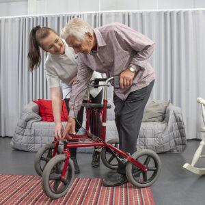 Kuvituskuva, jossa nuori hoitaja auttaa vanhusta rollaattorin kanssa, Hoitaja hymyilee vanhukselle lämpimästi.