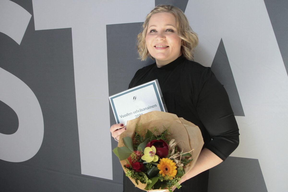Soilimaria Korhonen hymyilee kameralle kädessään kukkakimppu sekä palkintodiplomi.