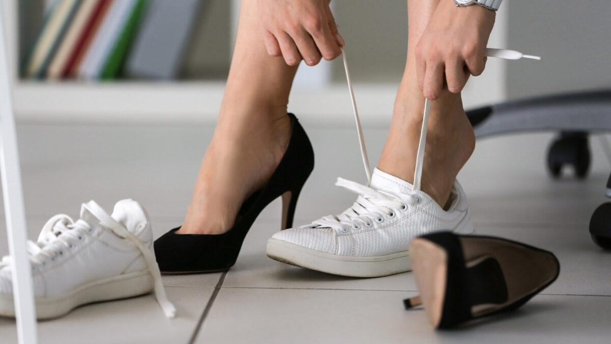 nainen solmii kenkää ja toisessa jalassa korkokenkä