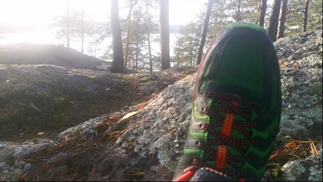 Kuvituskuvassa näkyy juoksukengän kärki kalliolla. Kauempana taustalla näkyy järvimaisema ja mäntyjen runkoja.