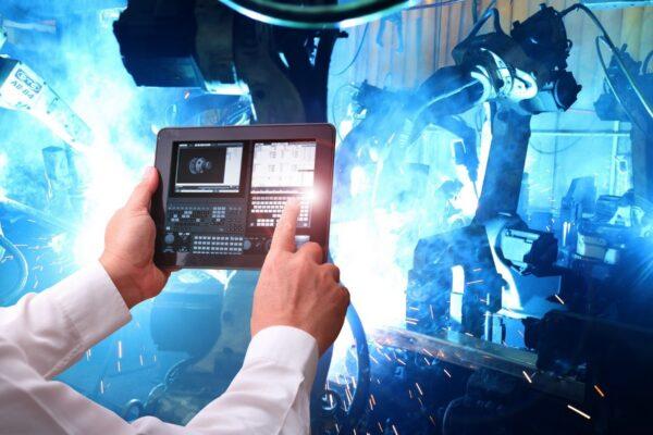 Kuvituskuva. Henkilön kädet näkyvät tablet-tietokoneen päällä ja tabletin taustalla kipinät räiskyvät sinisen sävyisessä konehuoneessa, kun hitsausrobotit työskentelevät.