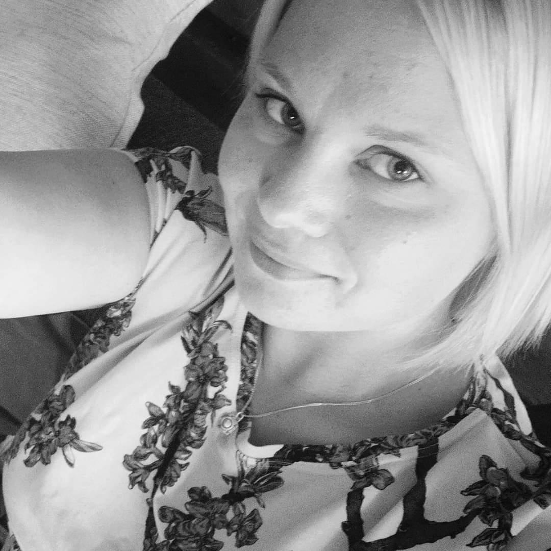 Marjo Kallio katsoo kameraan yläviistoon ja hymyilee vienosti. Kuva on mustavalkoinen.