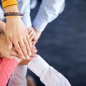 Kuvituskuvassa näkyy käsiä, joiden kämmenet on asetettu päällekkäin kuin yhteisen sopimuksen sinetöimiseksi.