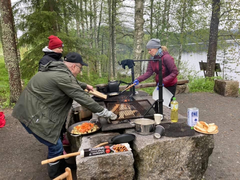 """Kuvassa kolme ihmistä valmistaa ulkona ruokaa avotulella isoista kivenlohkareista kyhätyssä """"keittiössä""""."""