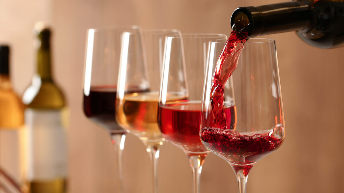 Punaviinin kaato ja taustalla viinilaseja