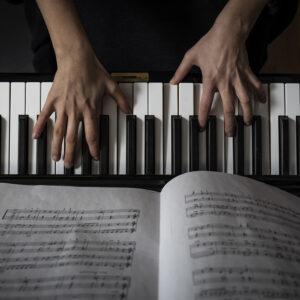 Kuvituskuva. Pianon koskettmien päällä näkyvät sormet ja kuvan alalaidassa nuottivihko, joka on auki soittajalle.