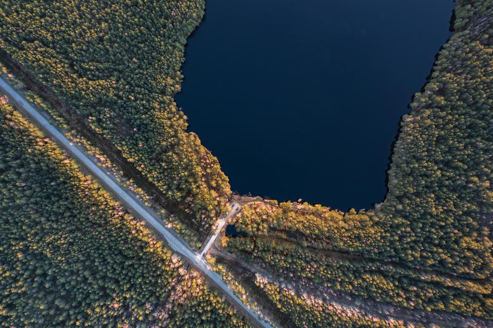 Kuvituskuvassa kuvattu järvimaisema ylhäältä käsin, kuvassa näkyy järven lisäksi metsää ja maantietä.