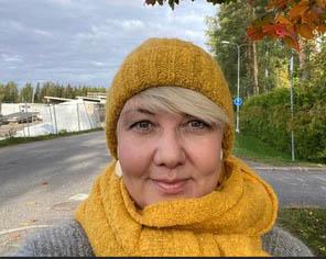 Riikka Vikström, lähikuva. Riikka katsoo kameraan ja hymyilee vienosti. Riikalla on kirkkaan keltainen kaulahuivi ja pipo ja hänen takanaan näkyy syksyinen maisema.