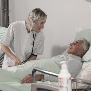 Sairaanhoitaja hoitaa sängyssä makaavaa potilasta