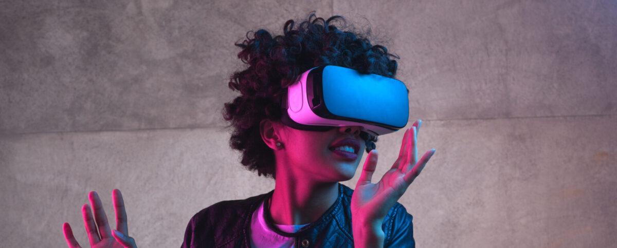 Kuvituskuva. Naine seisoo VR-lasit päässään ja katsoo kuvan oikealle puolelle kädet ilmassa.