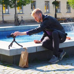 Tubettaja Roni Bäck istuu Kuopion torin laidalla olevan suihkulähteen reunalla ja asettelee kameraansa sopivaan kulmaan.